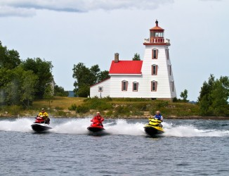 Three riders pass a lighthouse on the North Channel Sea Doo tour