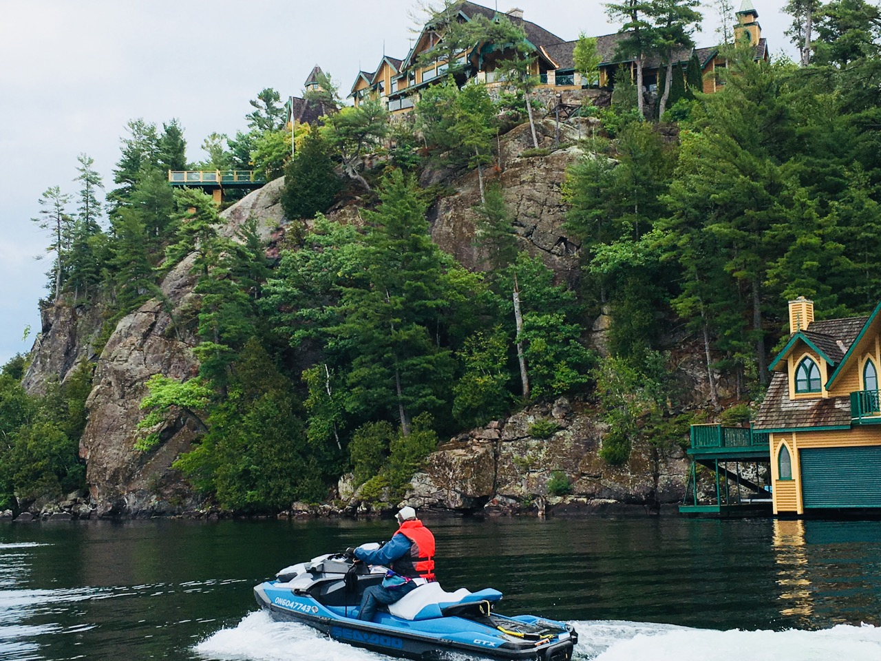Cruising past cottage on a cliff on Muskoka fall Sea Doo tour